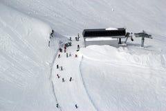 Gli sciatori e gli snowboarders che guidano su uno sci pendono Fotografia Stock Libera da Diritti