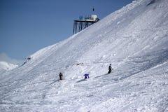Gli sciatori e gli snowboarders che guidano su uno sci pendono Immagini Stock