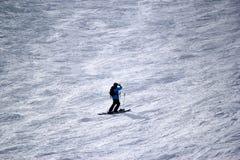 Gli sciatori e gli snowboarders che guidano su uno sci pendono Fotografie Stock
