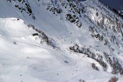 Gli sciatori e gli snowboarders che guidano su uno sci pendono Immagine Stock