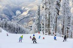 Gli sciatori e gli snowboarders guidano sul pendio dello sci nella stazione sciistica della montagna di Soci sul fondo scenico de immagine stock