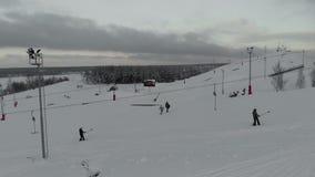 Gli sciatori e gli snowboarders scalano la collina sulla collina nella stazione sciistica Siluetta dell'uomo Cowering di affari 4 stock footage