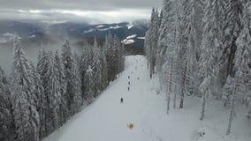 Gli sciatori e gli snowboarders scendono il pendio in una stazione sciistica archivi video