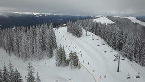 Gli sciatori e gli snowboarders scendono il pendio in una stazione sciistica Bukovel, Ucraina archivi video