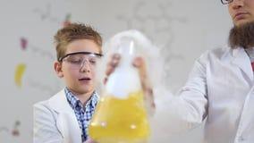 Gli scienziati esamina cocenti a vapore il liquido giallo stock footage