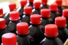 Gli sciroppi di frutta rosso scuro in bottiglie di plastica con i coperchi rossi sono pronti per distribuzione immagine stock libera da diritti