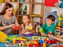Gli scolari con le forbici in bambini passa la carta di taglio immagine stock