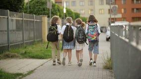 Gli scolari, ragazzi e ragazze, vanno a scuola con gli zainhi Vista posteriore Di nuovo alla scuola, giorno di conoscenza stock footage