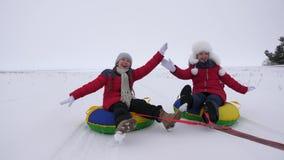 Gli scorrevoli dei bambini in neve su un tubo gonfiabile della neve e le onde passano Scorrevoli felici delle ragazze attraverso  immagine stock