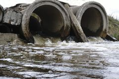 Gli scorrimenti dell'acqua delle acque luride tramite il vecchio tubo Fotografia Stock Libera da Diritti