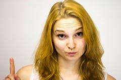 Gli sguardi dai capelli rossi della ragazza alla macchina fotografica alza il suo dito su immagini stock libere da diritti