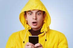 Gli sguardi di sguardo piacevoli colpiti allo Smart Phone, controlli del maschio il suo conto bancario online, rend contoere che  Immagine Stock