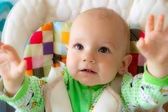 Gli sguardi di un anno del bambino ed alza le maniglie su Piccolo ragazzo allegro in un vestito verde chiaro con le pecore fotografia stock libera da diritti