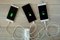 Gli Smartphones sono fatti pagare parallelamente dal caricatore e dalla bugia fotografia stock libera da diritti