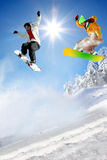 Gli Snowboarders che saltano contro il cielo blu Fotografie Stock Libere da Diritti
