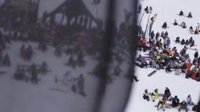 Gli Snowboarders e gli sciatori applaudono dentro campeggiano Stazione sciistica Bandiera nera d'ondeggiamento stock footage