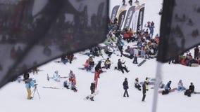 Gli Snowboarders e gli sciatori si rilassano dentro campeggiano Stazione sciistica Bandiera d'ondeggiamento prima della macchina  stock footage