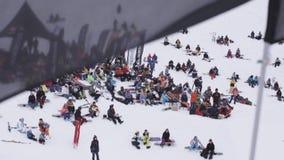 Gli Snowboarders e gli sciatori si rilassano dentro campeggiano Stazione sciistica Bandiera nera d'ondeggiamento archivi video