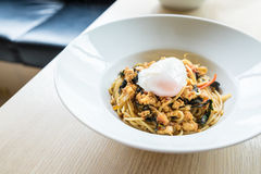Gli spaghetti caldi ed il pollo fritto del basilico riempiono con onsen l'uovo su w Fotografie Stock