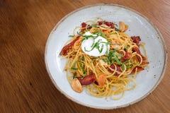 Gli spaghetti con bacon ed aglio e peperoncini rossi croccanti hanno completato con il po fotografia stock libera da diritti