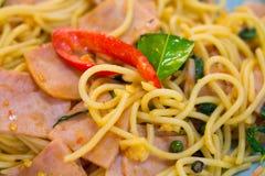 gli spaghetti con bacon, la salsiccia ed il basilico croccanti fritti vanno, alimento caldo e piccante, cucina internazionale Fotografie Stock