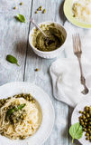 Gli spaghetti con il pesto sauce sul piatto d'annata bianco, sul formaggio grattugiato, sulle foglie fresche del basilico e sui f Immagini Stock Libere da Diritti