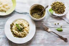 Gli spaghetti con il pesto sauce sul piatto d'annata bianco, sul formaggio grattugiato, sulle foglie fresche del basilico e sui f Immagini Stock