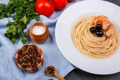 Gli spaghetti con le olive e gamberetti, ciliegia, prezzemolo, peperoni e un saltcream sulla tavola Fotografia Stock Libera da Diritti
