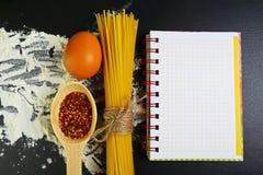 Gli spaghetti della pasta, gli alimenti italiani concetto e la progettazione del menu, le spezie sui cucchiai di legno, le uova c fotografia stock libera da diritti