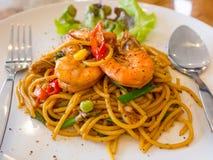 Gli spaghetti, gamberetto hanno fritto i peperoni su un piatto bianco Sulla tavola di legno Fotografie Stock Libere da Diritti