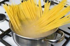 Gli spaghetti hanno cucinato in acqua bollente su una stufa di gas L'alimento italiano tradizionale Fotografie Stock