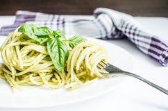 Gli spaghetti italiani della pasta con la salsa ed il basilico casalinghi di pesto coprono di foglie Fotografia Stock
