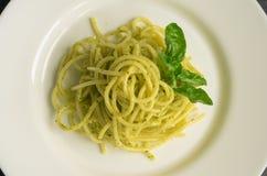 Gli spaghetti italiani della pasta con la salsa ed il basilico casalinghi di pesto coprono di foglie Immagini Stock
