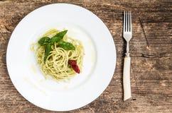 Gli spaghetti italiani della pasta con la salsa ed il basilico casalinghi di pesto coprono di foglie Fotografie Stock Libere da Diritti