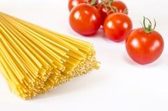 Gli spaghetti si trovano su un fondo bianco, con i pomodori ciliegia fotografia stock