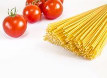 Gli spaghetti si trovano su un fondo bianco, con i pomodori ciliegia immagini stock