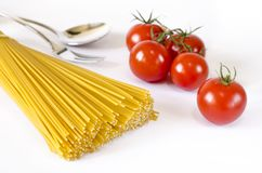 Gli spaghetti si trovano su un fondo bianco, con i pomodori ciliegia fotografia stock libera da diritti