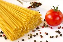 Gli spaghetti si trovano su un fondo bianco, con i pomodori ciliegia fotografie stock libere da diritti