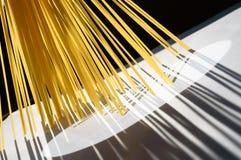 Gli spaghetti stanno verticalmente nell'ambito della luce solare su bianco Fotografia Stock