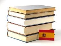 Gli Spagnoli diminuiscono con il mucchio dei libri su fondo bianco immagine stock libera da diritti
