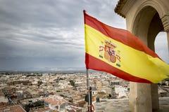 Gli Spagnoli inbandierano l'ondeggiamento sopra la città di Cox, Alicante, Spagna Immagine Stock