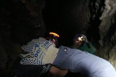 Gli speleologi nella caverna illuminano il loro modo con i fari Fotografia Stock Libera da Diritti