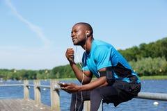 Gli sport americani equipaggiano l'esterno di seduta che ascolta la musica Fotografie Stock Libere da Diritti