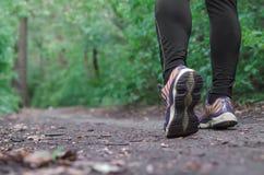 Gli sport calza la camminata o pareggiare sull'erba verde, funzionamento del paese trasversale del corridore dell'uomo sulla trac Fotografie Stock