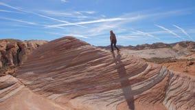 Gli sport che fanno un'escursione la donna scala i precedenti rossi della roccia il cielo Immagini Stock