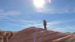Gli sport che fanno un'escursione la donna scala i precedenti rossi della roccia il movimento lento 4K del cielo video d archivio