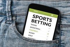 Gli sport che scommettono il concetto sullo schermo dello smartphone in jeans intascano fotografia stock