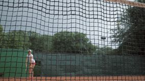 Gli sport che vincono, ragazza del tennis professionista batte la racchetta sulla palla ed i funzionamenti fino a rete con le man archivi video