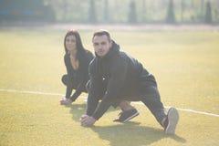Gli sport coppia l'allungamento del corpo nel parco Fotografie Stock
