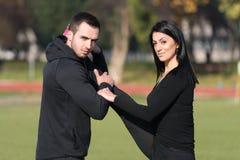 Gli sport coppia l'allungamento del corpo nel parco Immagini Stock Libere da Diritti